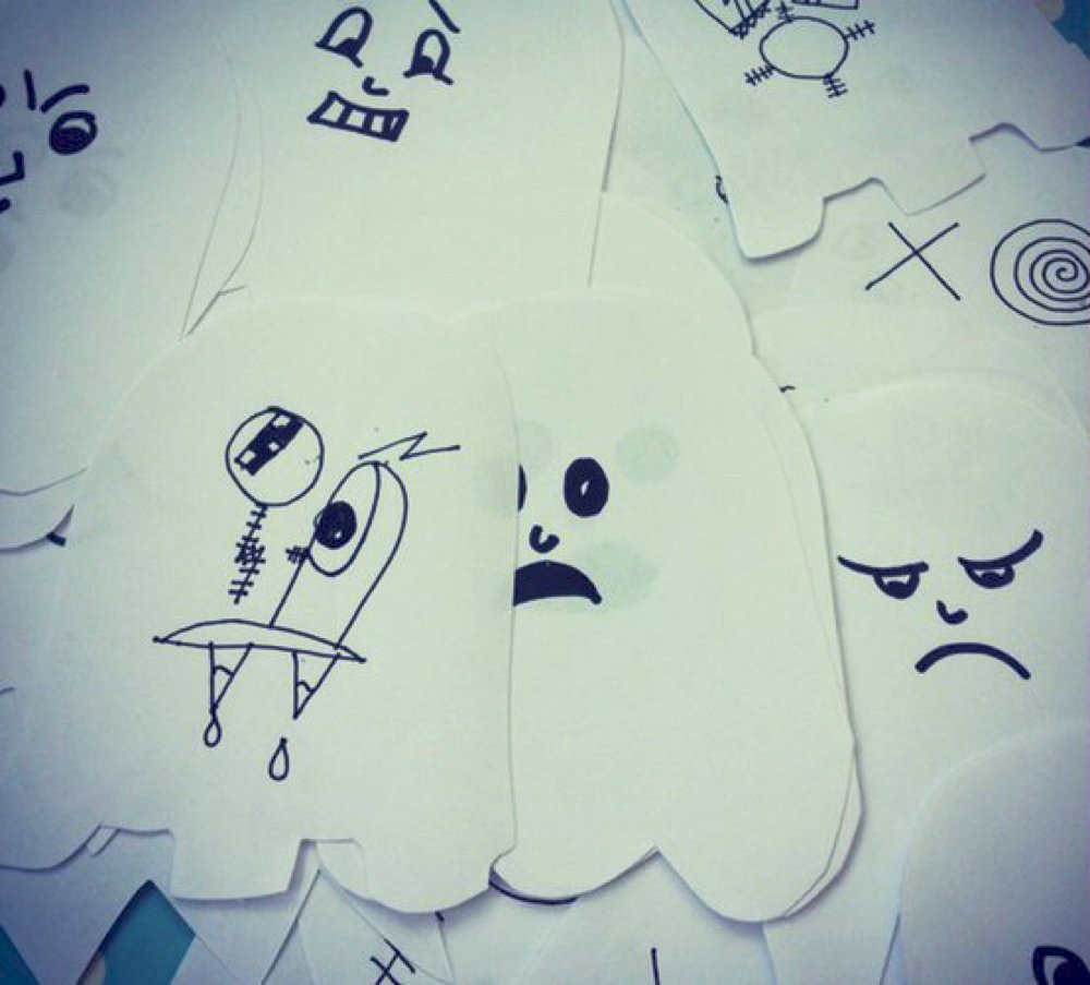 pile of paper ghosts cut out and with little faces on ready to make ghost garlands for Halloween