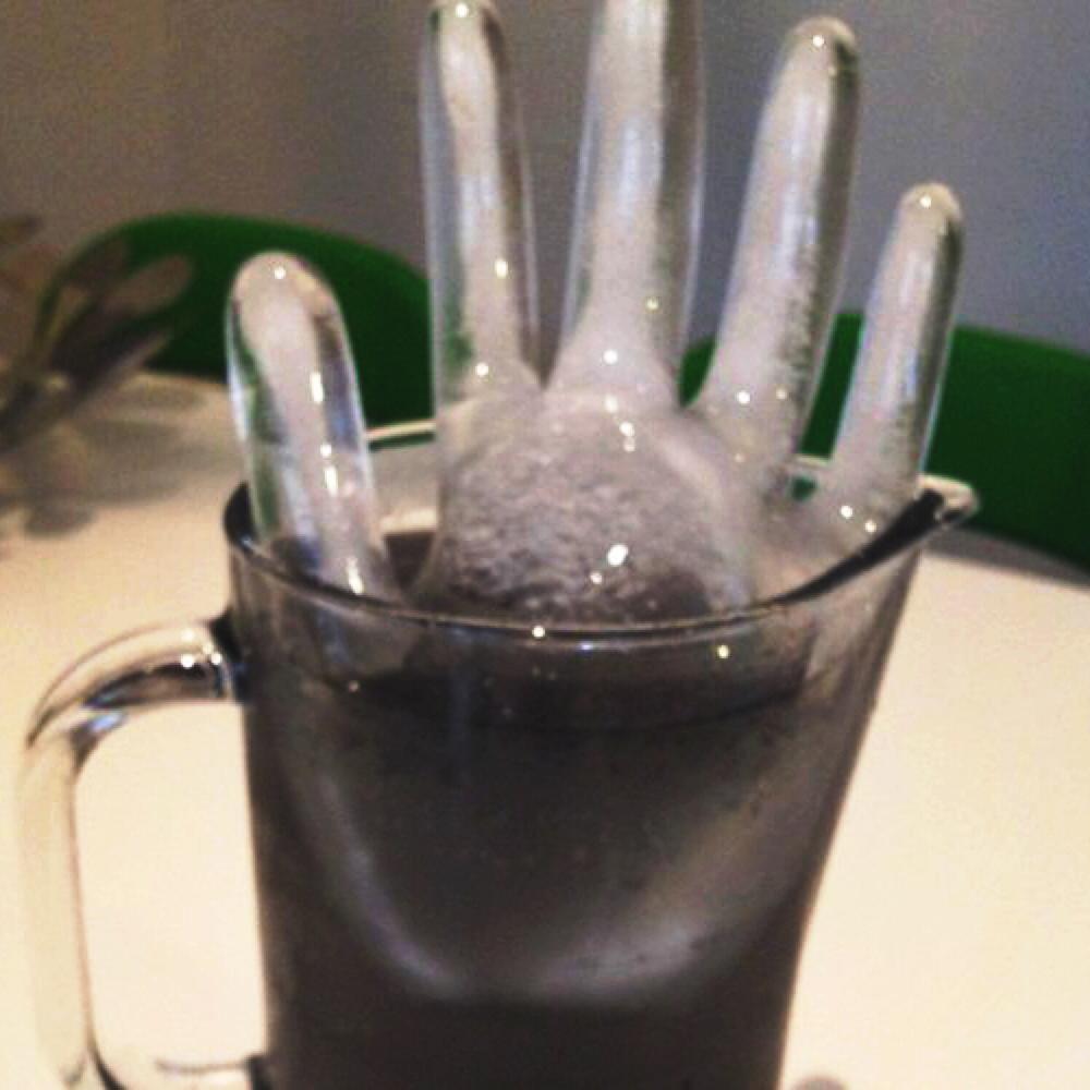 icy hand sculpture in a jug of black lemonade