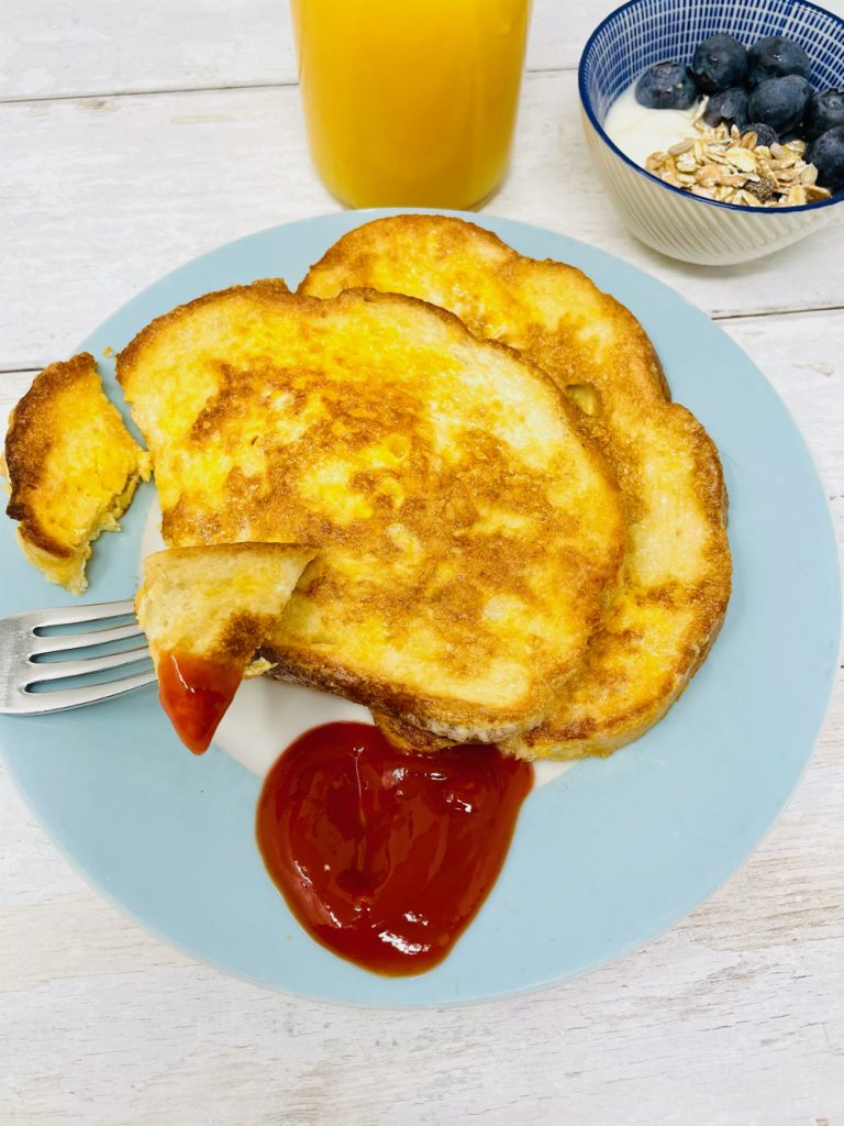eggy bread served with ketchup for breakfast alongside muesli and fruit and a bottle of orange juice