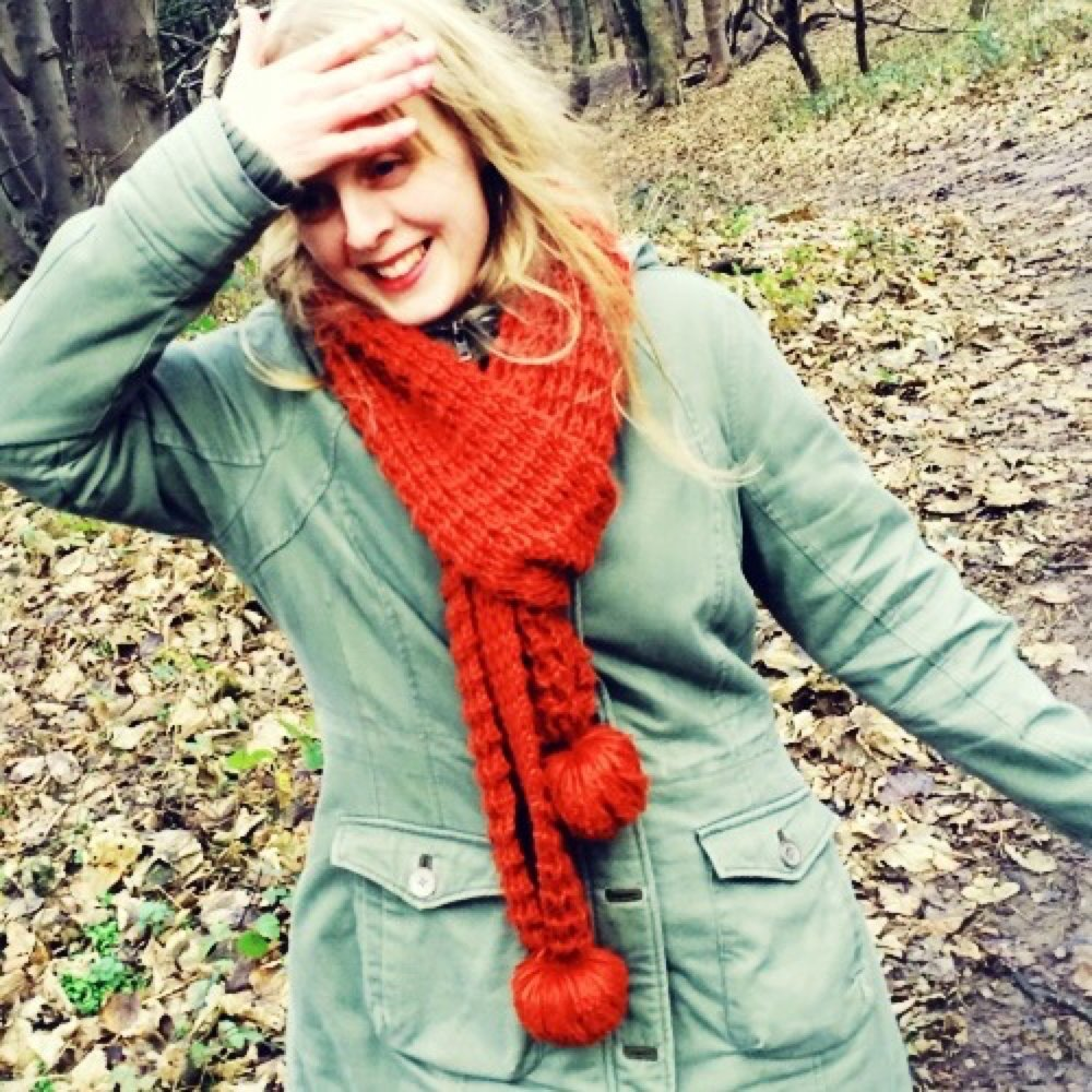 Blonde girl in green FatFace parka coat with orange scarf in the woods
