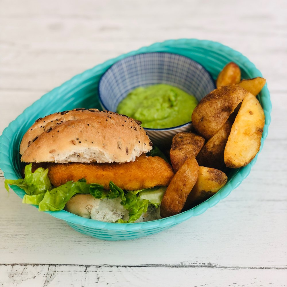 fish finger sandwich with oven baked wedges and creamy pesto pea dip served in a basket