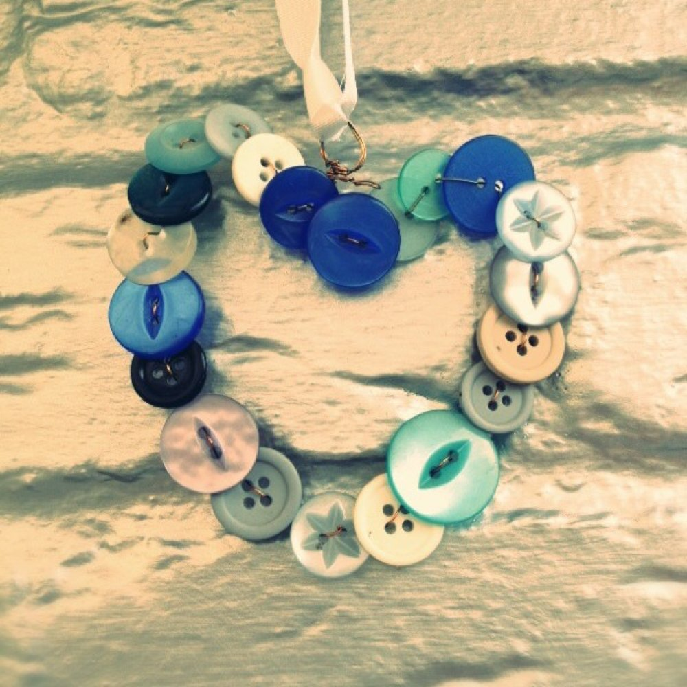 homemade heart decoration made from different shades and types of blue buttons held on wire and hung with a blue ribbon against a silver painted brick wall