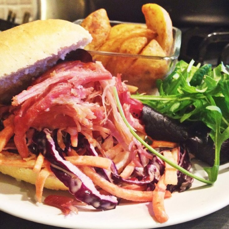 white plate with crusty bread roll filled with homemade coleslaw and pulled ham, pot of potato wedges and rocket salad also on the plate.