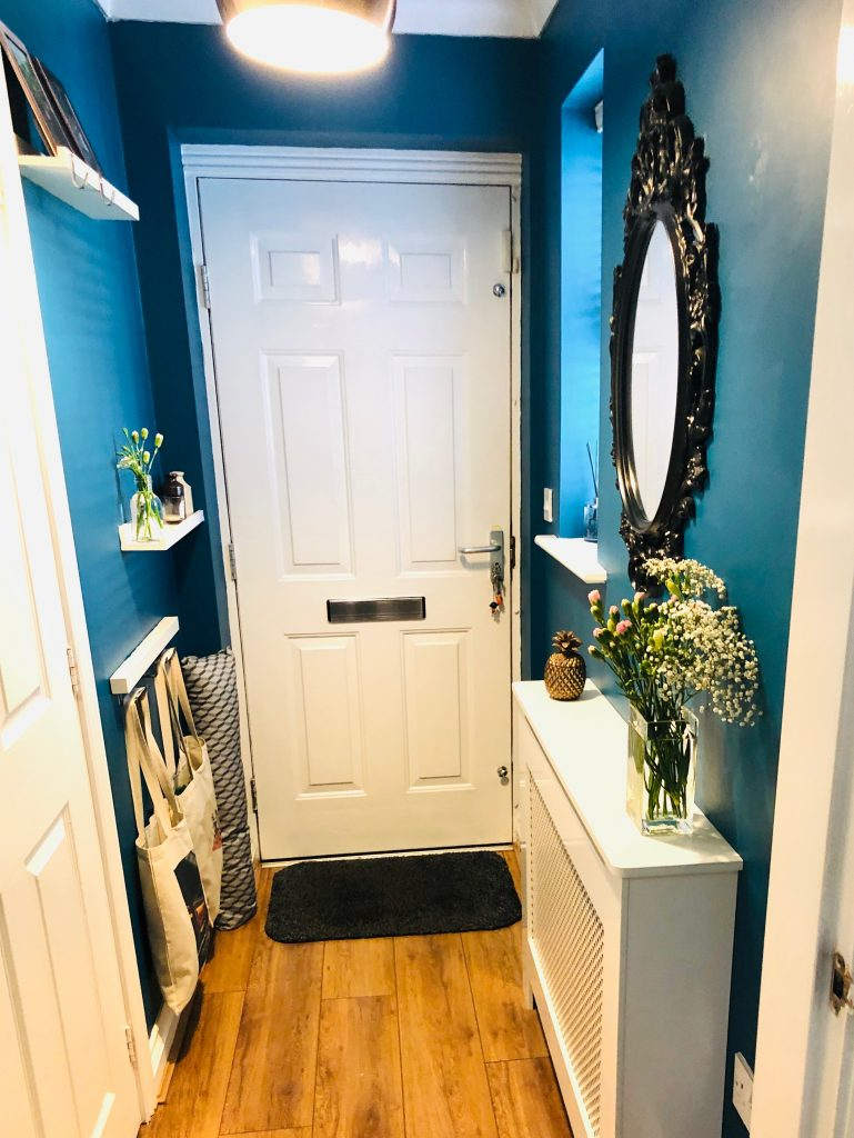 small hallway painted dark blue with gothic style mirror, picture shelves and radiator cover with bronze pineapple ornament and vase of gypsy grass and pink carnations - tote bags hung low down for storage.