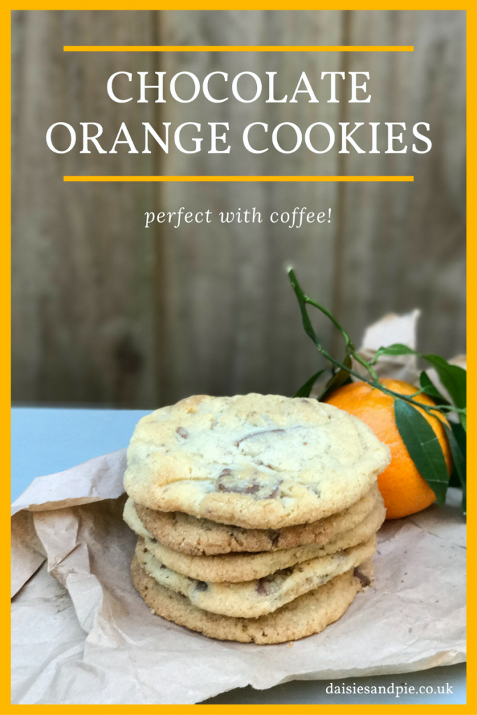 """Pile of Terry's chocolate orange cookies on brown paper next to an orange with leaves on it, brown wooden fence in the background. Text """"the most amazing chocolate orange cookies"""""""