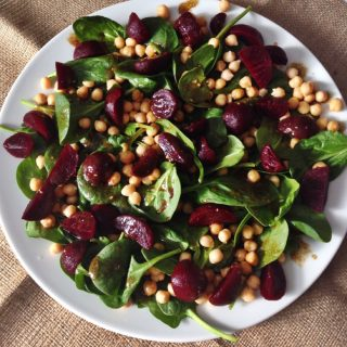 hessian table cloth with white plate holding spinach, beetroot and chickpea salad with Balsamic salad dressing drizzled over the top