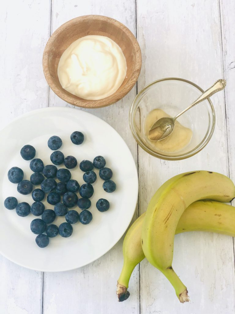 ingredients for blueberry smoothie pops - handful of blueberries, small wooden bowl filled with Greek yogurt, spoonful of honey and 2 ripe bananas