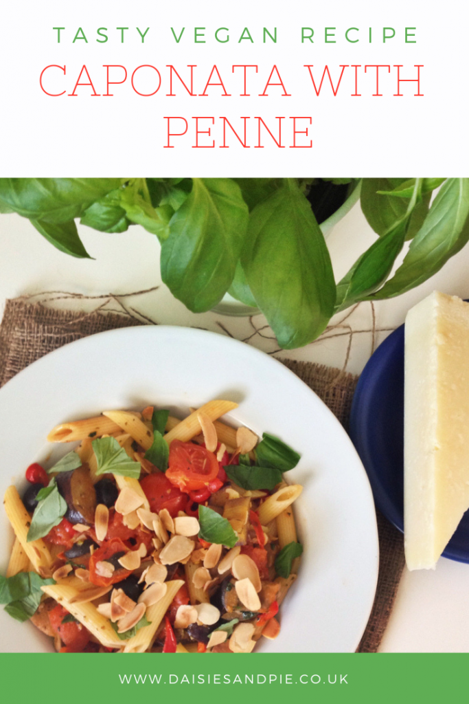 "freshly made caponata tossed through penne pasta sprinkled with toasted almonds. Text overlay saying ""tasty vegan recipe - caponata with penne"""
