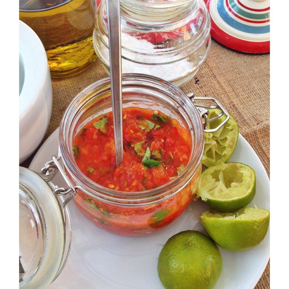 jar of homemade easy Mexican tomato salsa alongside lime halves.