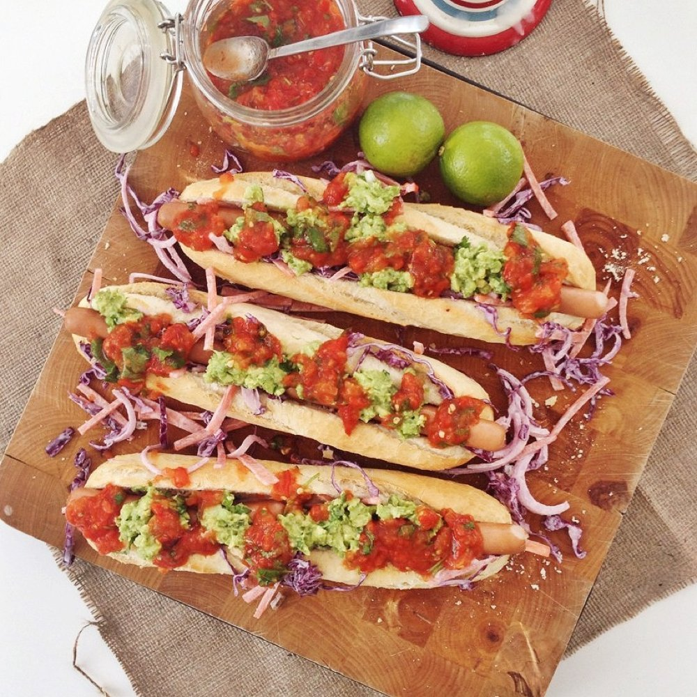 wooden board with three gourmet hot dogs served on crusty baguettes topped with homemade jalapeño slaw, roast mexican style salsa and homemade guacamole