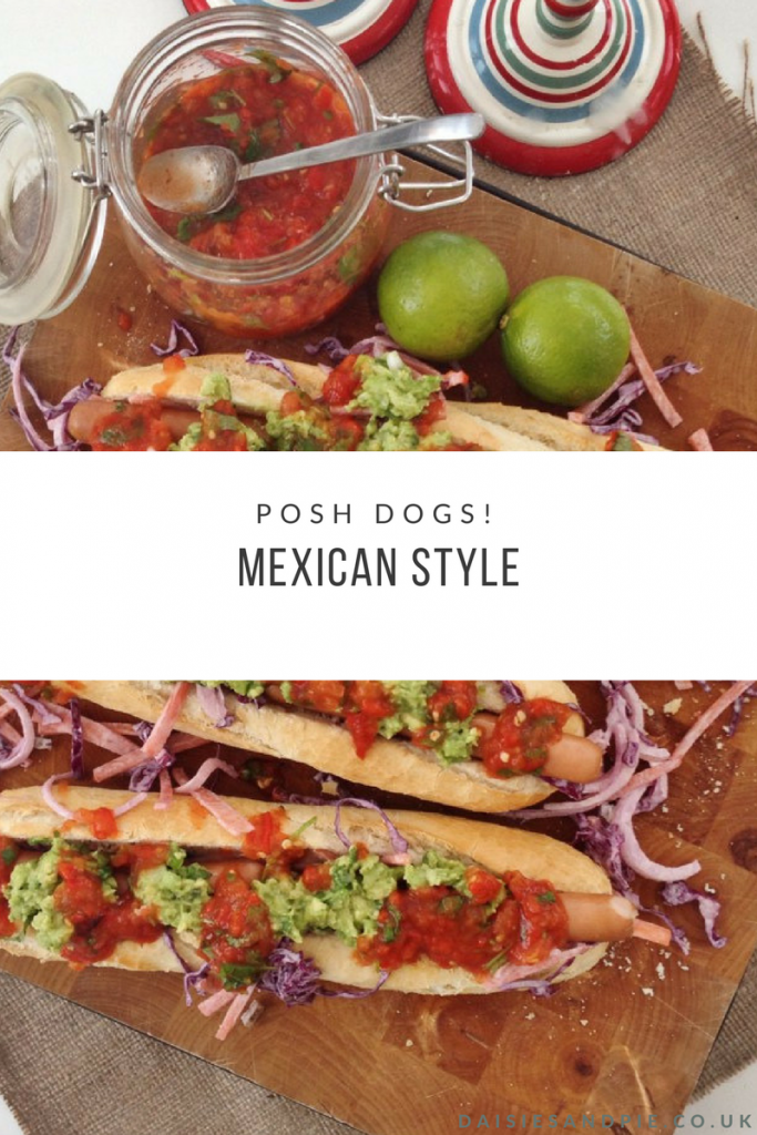 "wooden board with three gourmet hot dogs served on crusty baguettes topped with homemade jalapeño slaw, roast mexican style salsa and homemade guacamole. Text overlay saying ""posh dogs mexican style"""