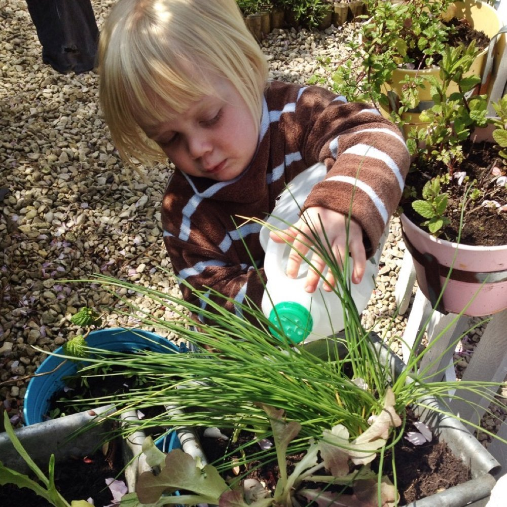toddler watering plants with milk bottle watering can