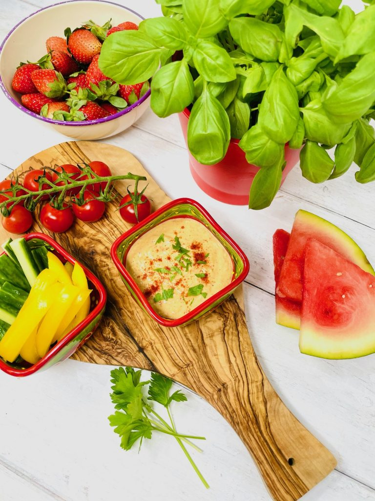 red pepper hummus in a tapas bowl served with cucumber and yellow pepper sticks, cherry vine tomatoes and watermelon slices