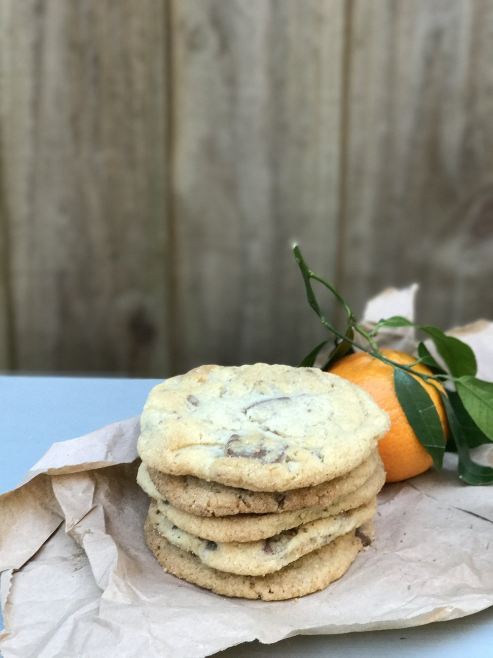 Pile of Terry's chocolate orange cookies on brown paper next to an orange with leaves on it, brown wooden fence in the background