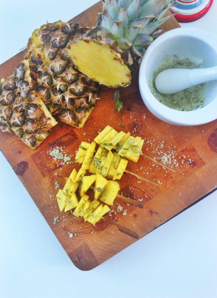 wooden board with grilled pineapple skewers sprinkled in mint sugar