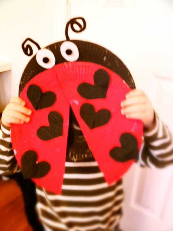 toddler holding up a ladybird made from paper plates with love hearts on the red wings instead of spots