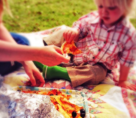 pack a picnic, toddler eating pizza on a picnic
