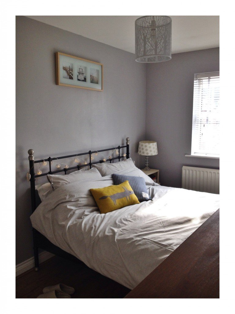 calm light bedroom, iron bed, grey bedding, yellow dog cushion, laura ashley lamp