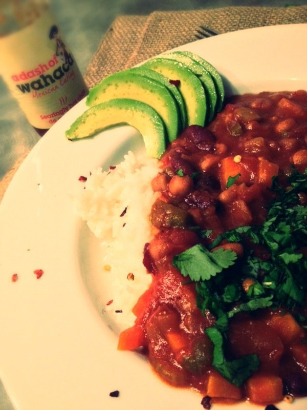 slow cooker vegetarian chilli served with rice and sliced avocado
