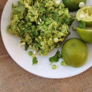 white plate with pile of homemade guacamole alongside some lime halves