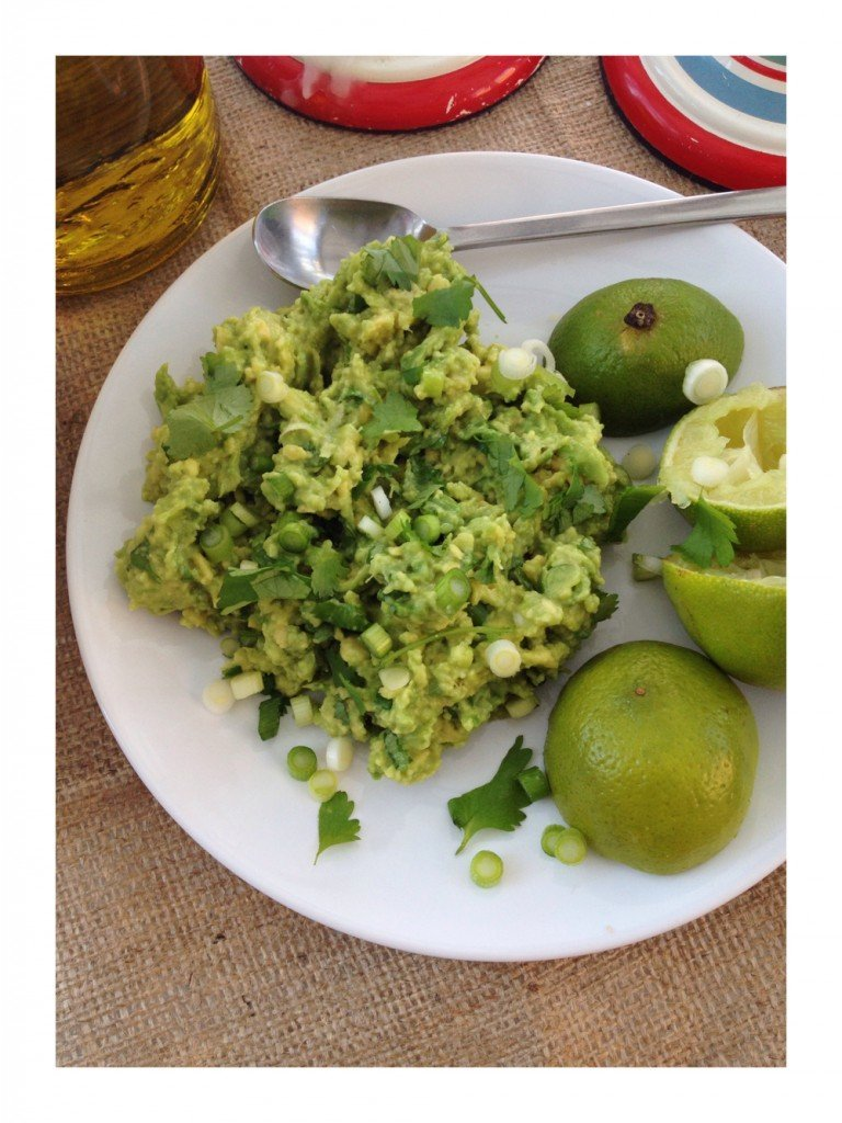 homemade guacamole with avocado, spring onions and corianders and lime