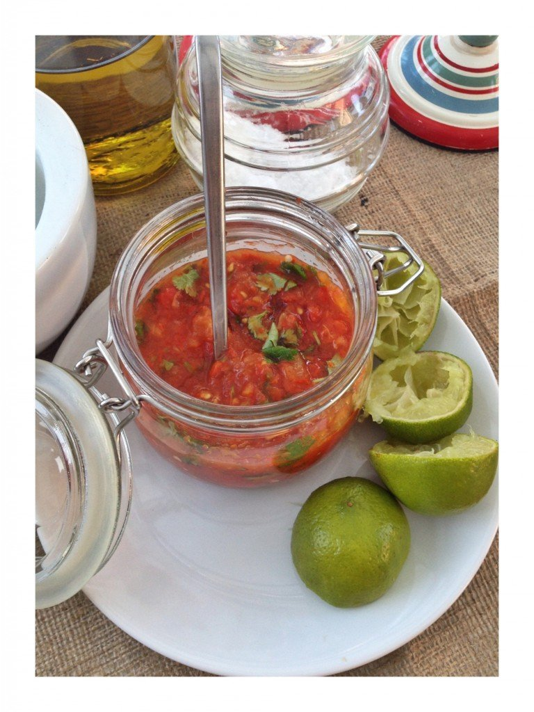 homemade Mexican roast tomato salsa in a glass jar with sea salt and lime wedges by the side