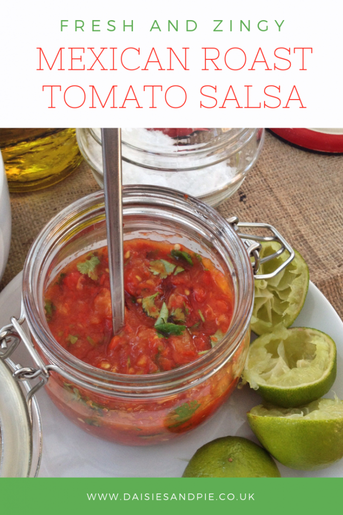 homemade mexican roast tomato salsa in a glass jar alongside a jar of sea salt and lime halves
