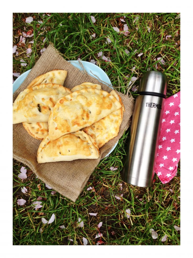 plate of homemade vegetarian pasties set on the grass alongside thermos flask and red napkin with white stars on it. Grass is speckled with blossom petals