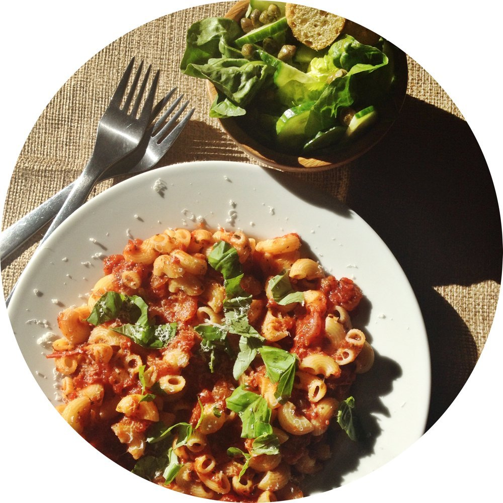 homemade tomato pasta in a white bowl with green salad on the side