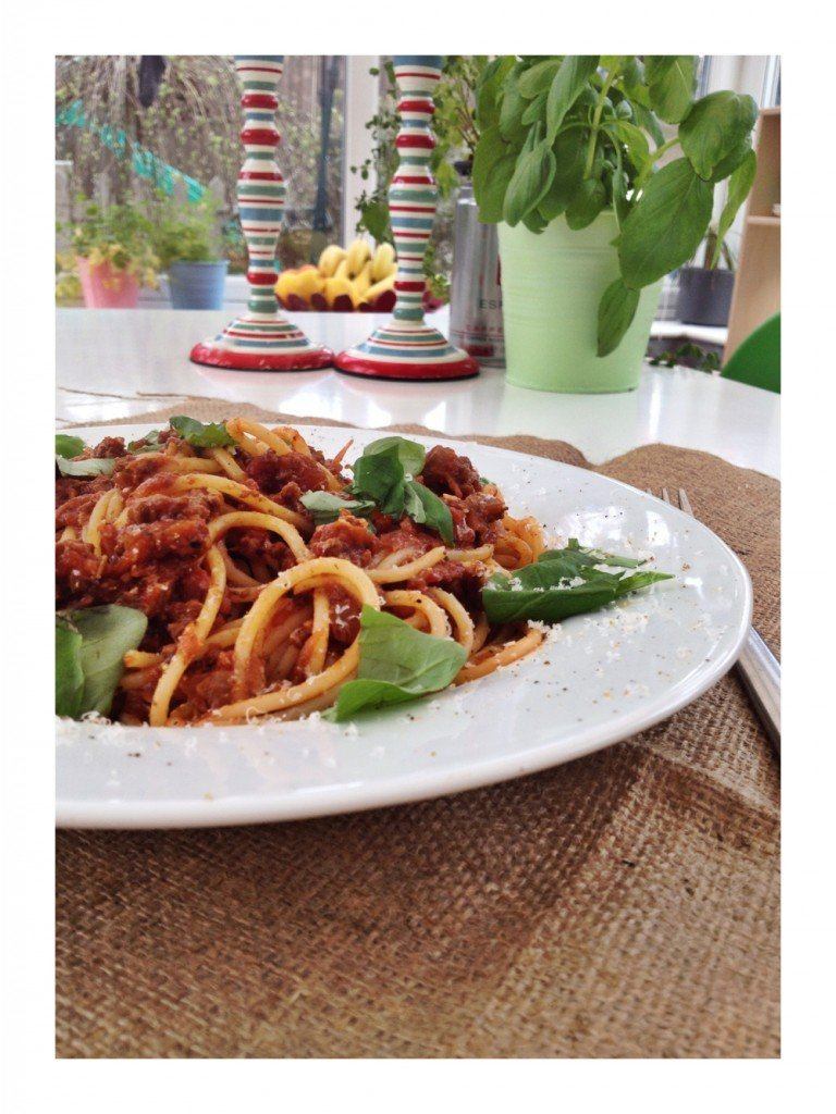 homemade proper italian spaghetti bolognese served scattered with basil leaves