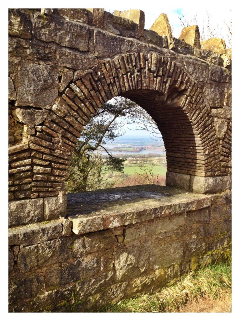 View of Rivington Pike and surrounding Lancashire countryside through a stone arch window up Winter Hill in the terrace gardens