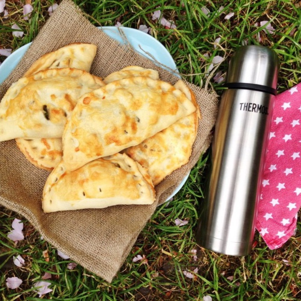 A pile of vegetable pasties lying on hessian sack on the blossom petal speckled grass. A silver thermos flask and red and white star napkin are alongside the pasties