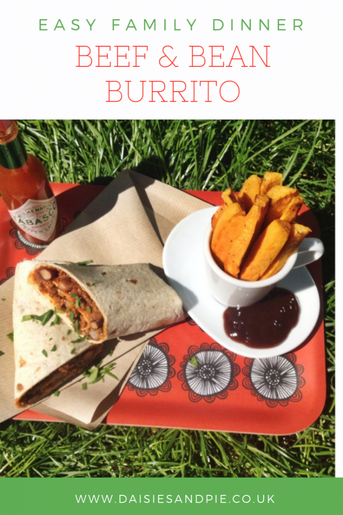 """red flowery tray with a homemade beef and bean burrito wrapped in paper alongside a pot of sweet potato wedges with BBQ dip. Text overlay saying """"easy family dinner - beef and bean burrito"""""""