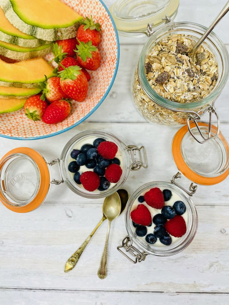 breakfast pots with cereal and yogurt with fruit served in little kilner jars.