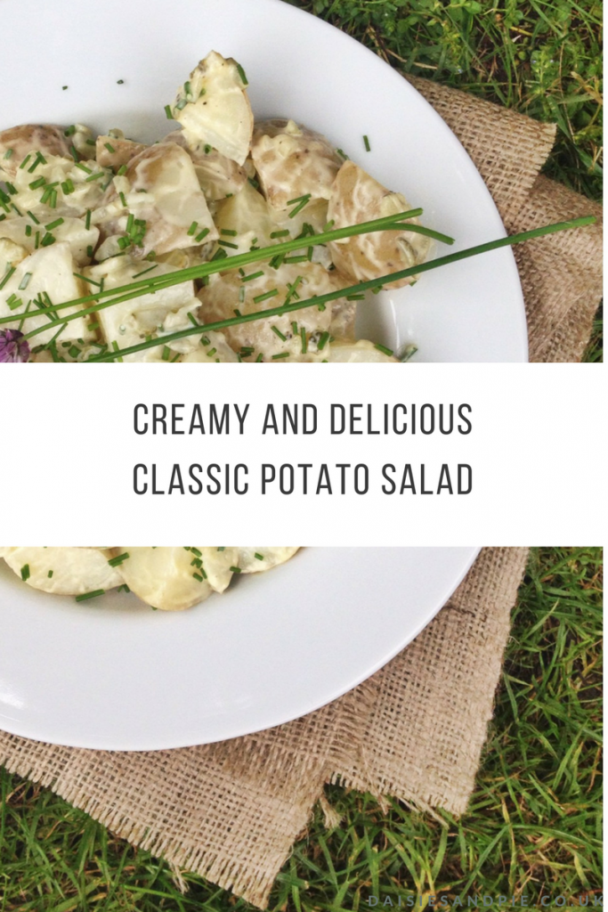 "plate of homemade potato salad with creamy dressing, chives and chive flowers on a hessian cloth on the grass. Text overlay saying ""delicious and creamy classic potato salad"""