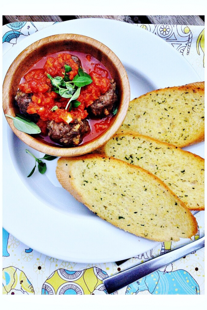 easy meatball recipe served in a wooden bowl with hidden veg tomato sauce and garlic bread dippers on the side for mopping up the juices