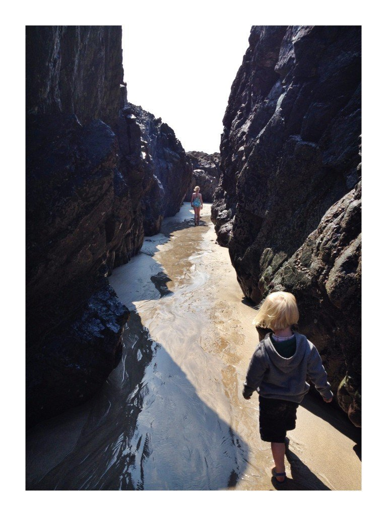 kids playing in the natural cave corridors at Kynance Cove Cornwall