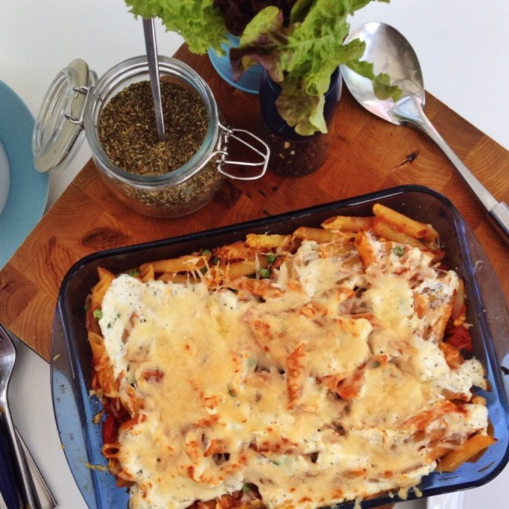 casserole dish filled with tuna pasta bake alongside salad and serving spoons.
