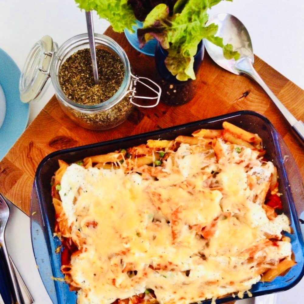 tuna pasta bake in a blue oven dish next to a jar or dried oregano and pot of growing salad leaves