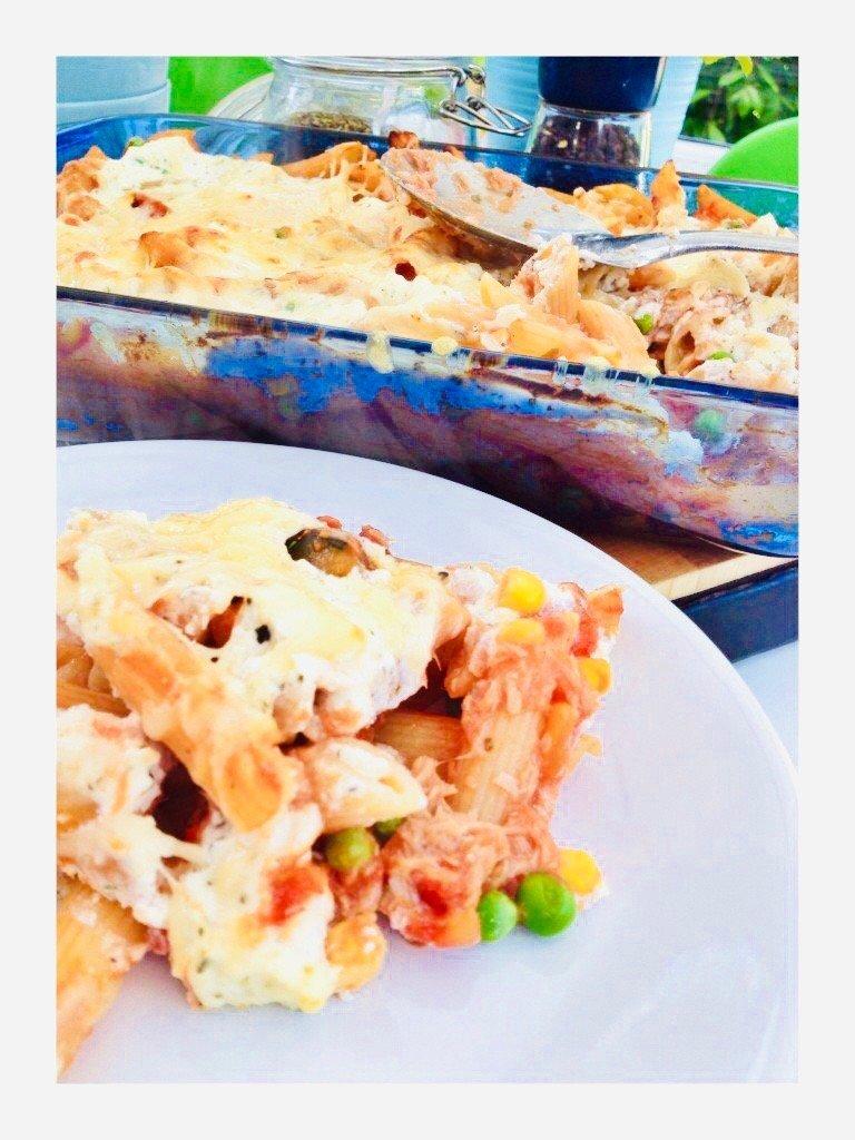 tuna pasta bake in a blue oven proof glass dish, with some served on a white plate