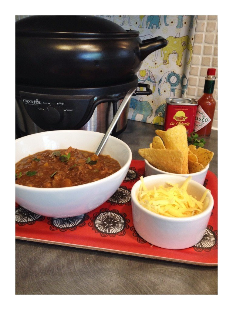 black crockpot with bowlful of BBQ mince and beans alongside nachos and shredded cheese