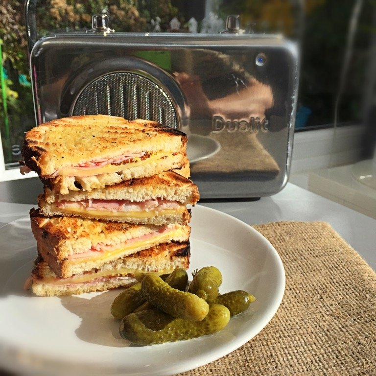 dutch style ham and cheese toasted sandwiches with cornichons in front of a Dualit silver radio