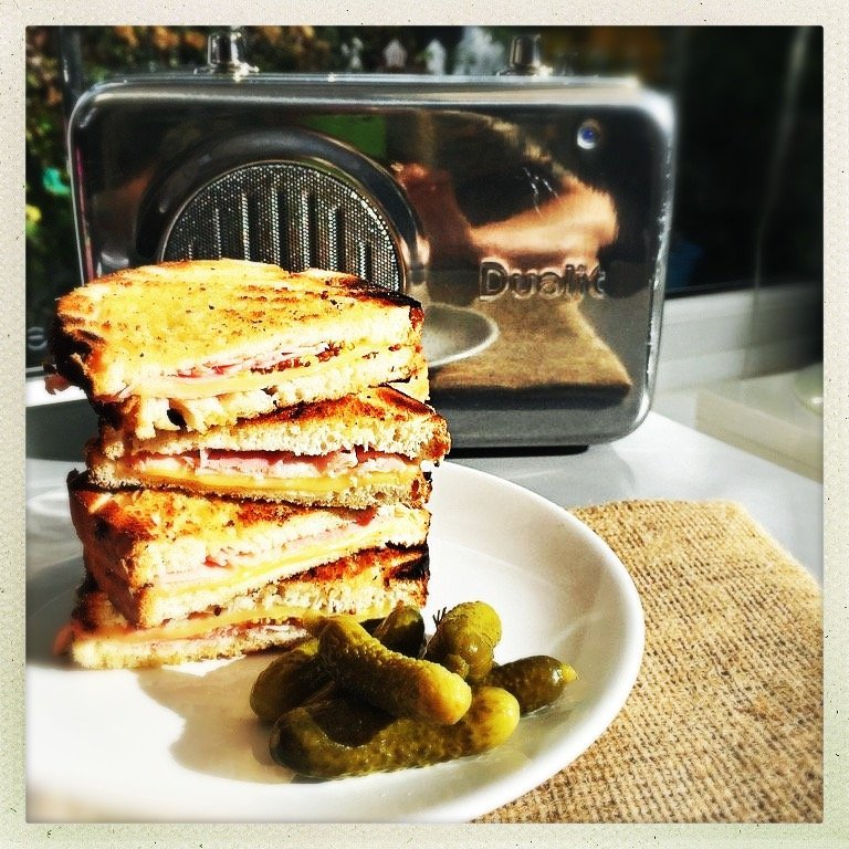toasted ham and cheese sandwiches piled up on a plate with a side of cornichons Dualit stainless steel radio in the background