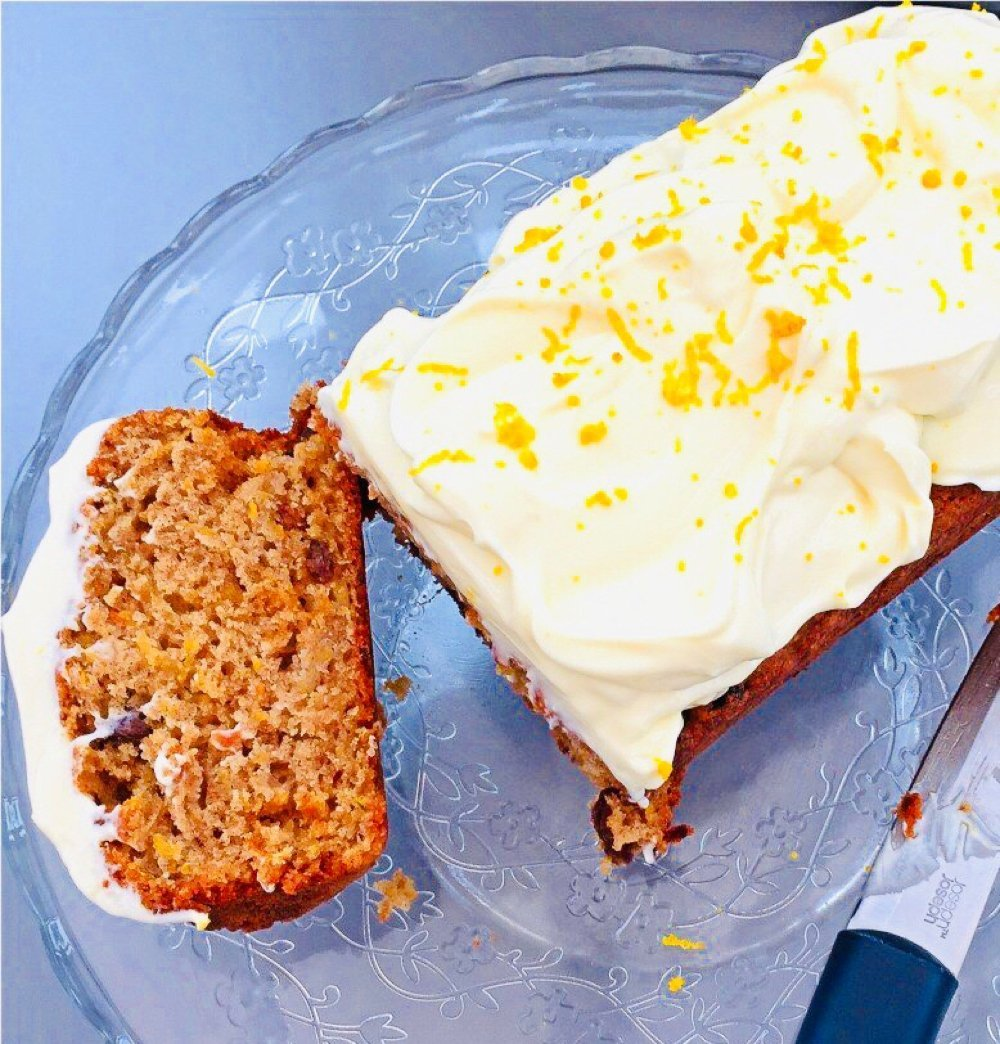 butternut squash cake with orange cream cheese frosting on a glass cake stand with a Joesph Joseph knife