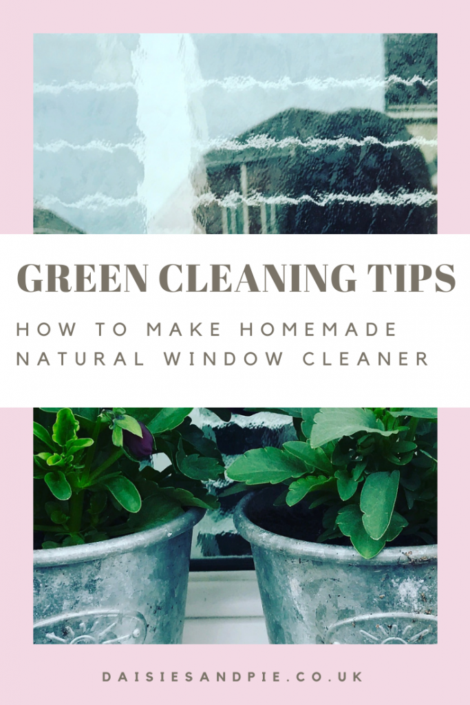 "shiny clean window with three silver pots on the windowsill filled with purple and white pansies. Text ""green cleaning tips - how to make homemade natural window cleaner - daisisandpie.co.uk"""
