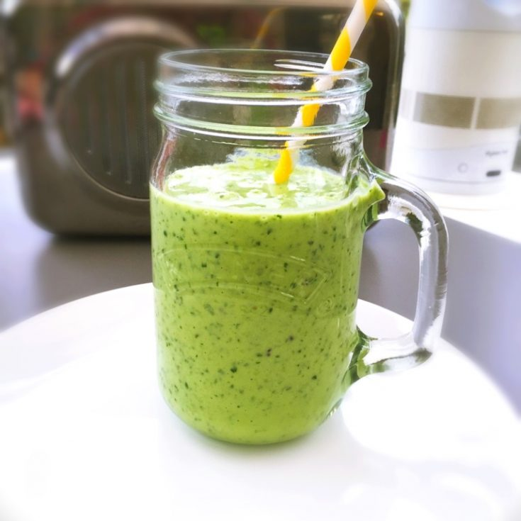 vivid green smoothie made from kiwi, spinach, banana and natural yogurt served in a glass kilner jar cup with a yellow and white paper straw