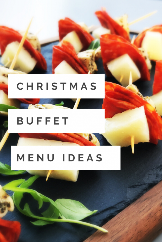 "wooden and slate food platter with mini homemade Italian skewers with chicken, chorizo and machego cheese on cocktail sticks - garnish with rocket leaves. Text ""Christmas buffet menu ideas"""