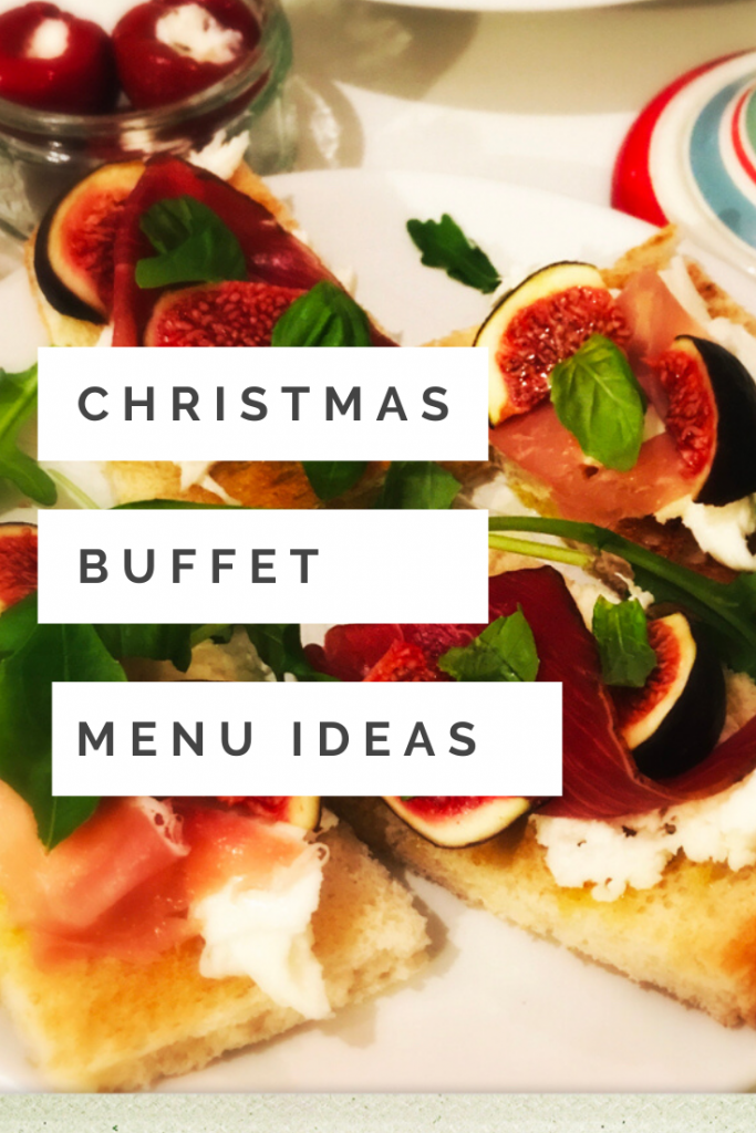 "platter of festive bruschetta made with sourdough toast topped with mozzarella, figs, parma ham and basil leaves. Small bowl of pepperdew ricotta cheese stuffed peppers in the background. text ""christmas buffet menu ideas"""