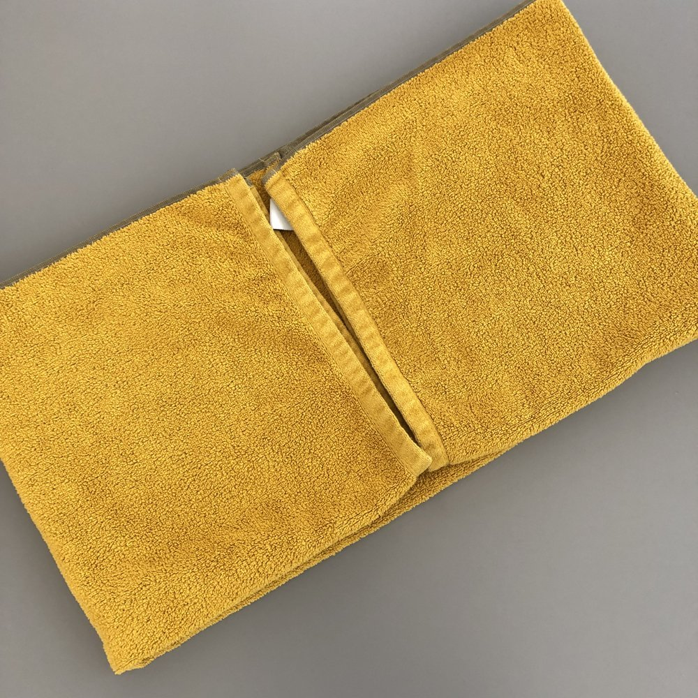 yellow towel being folded neatly
