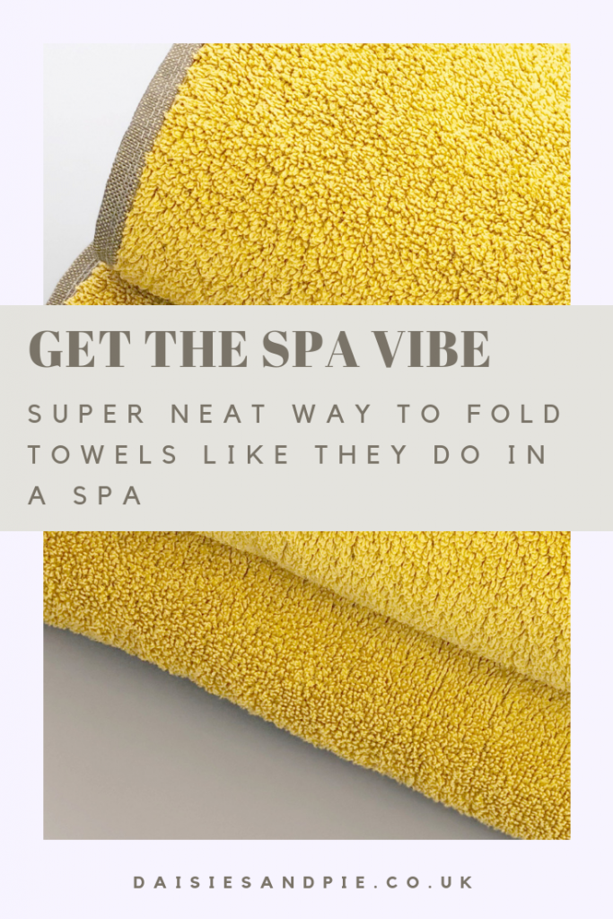 "pile of neatly folded yellow towels. Text overlay saying ""get the spa vibe - super neat way to fold towels like they do in a spa"""
